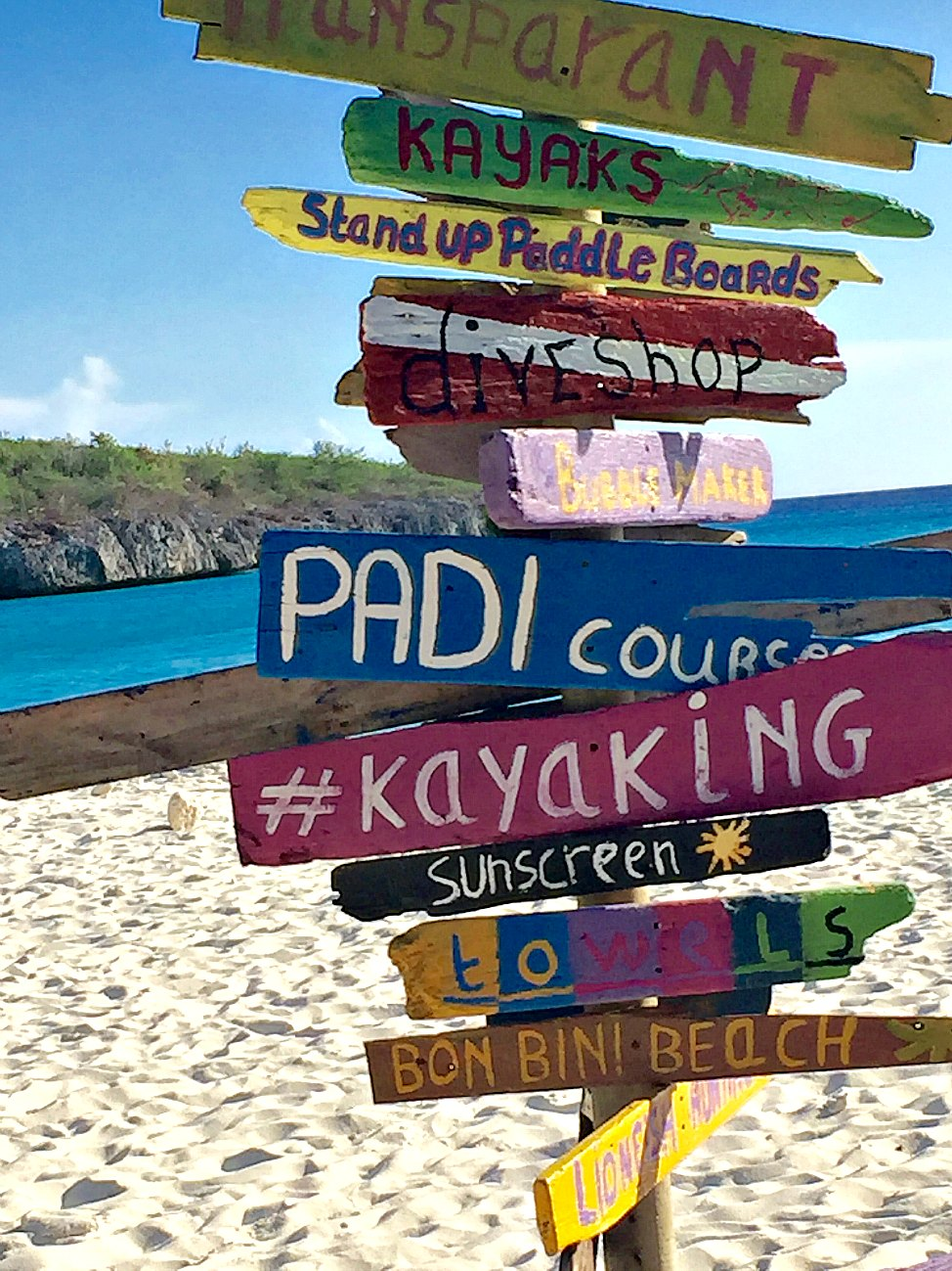 Colorful, rustic sign on the beach in Curaçao