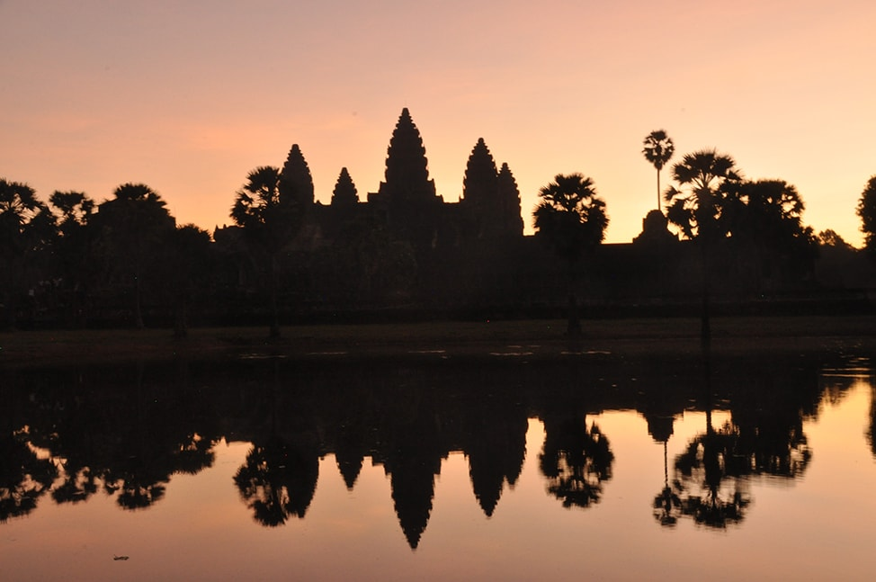 Silhouette of Angkor Wat against a pink sky at sunrise