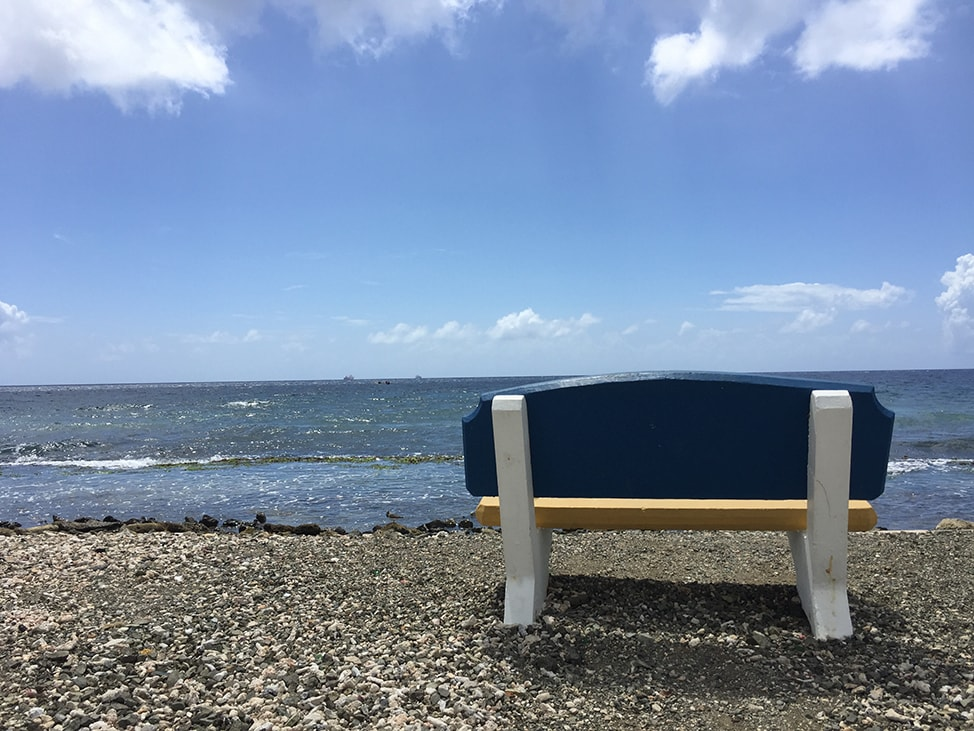 An empty bench along the water's edge in Curaçao