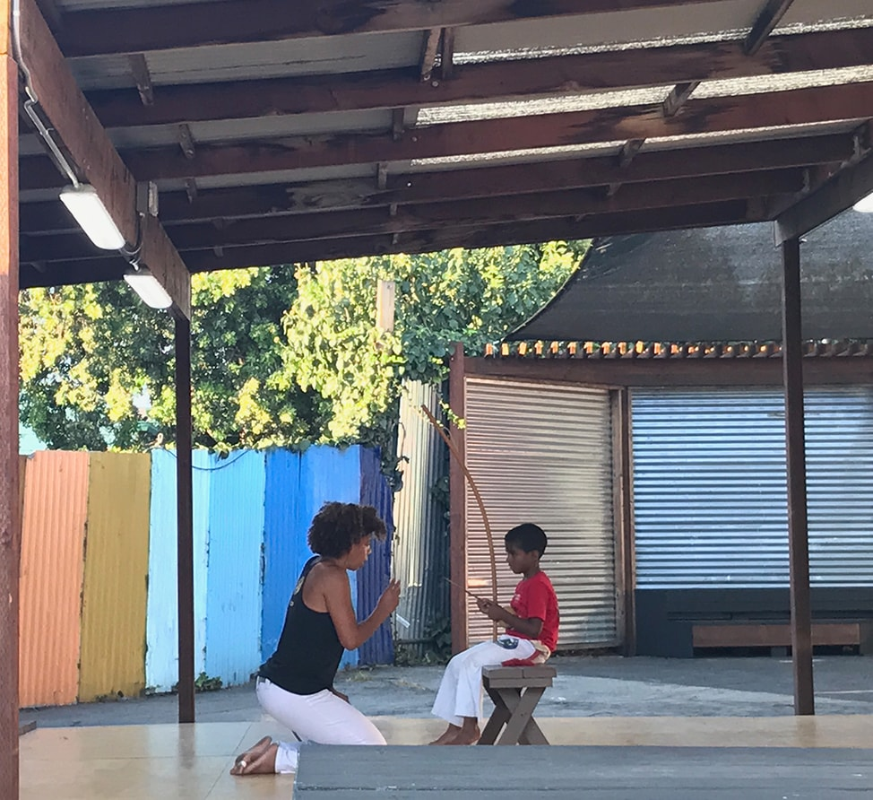 Teaching a child to play the berimbau as a part of capoeira class